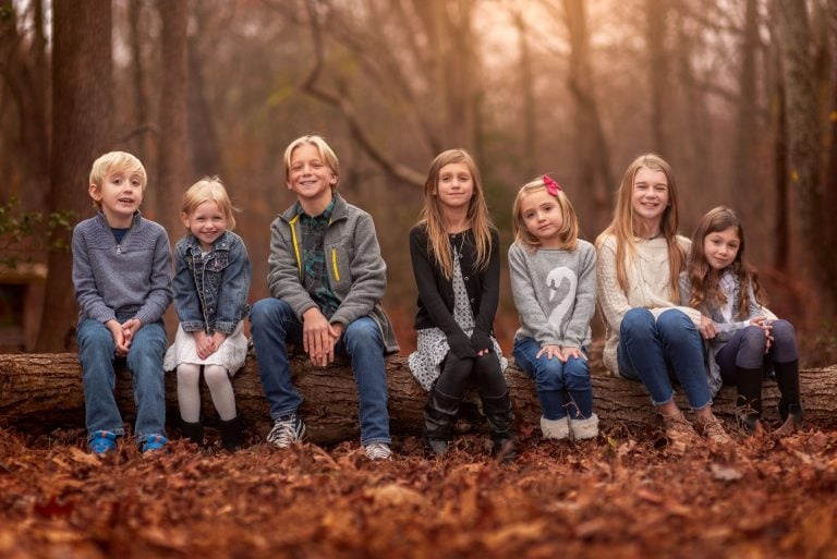 Kids sitting on a log at Allaire State park for a photography shoot