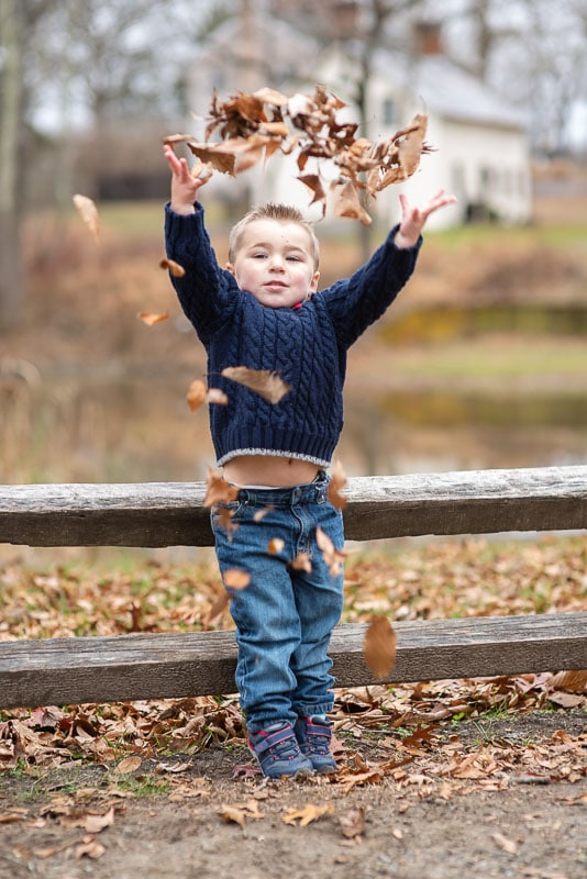 Young kid throwing up leaves during a family photo session at Allaire State Park