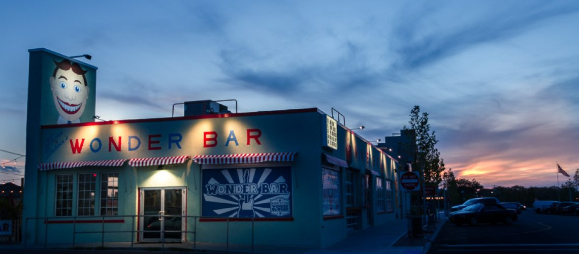 Wonder Bar in Asbury Park New Jersey during sunset with a pink sky and lights on outside the bar