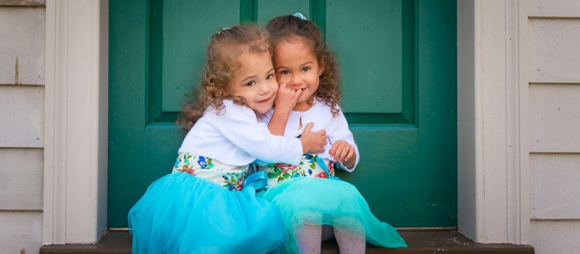 Two young twins hugging each other in front of an antique building while sitting on the steps